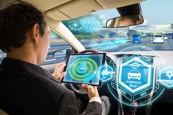 Man on a tablet device while in a driverless car.