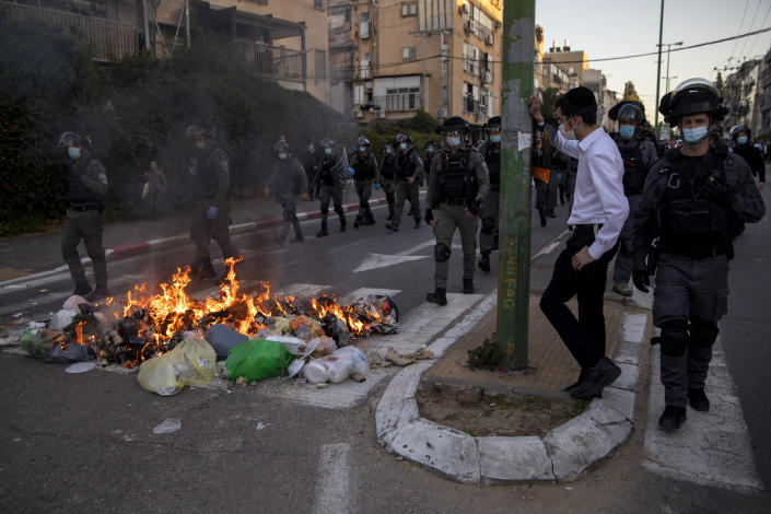 Israeli police officers march by burning garbage during clashes with ultra-Orthodox Jews in Bnei Brak, Israel, Sunday, Jan. 24, 2021. Ultra-Orthodox demonstrators clashed with Israeli police officers dispatched to close schools in Jerusalem and Ashdod that had opened in violation of coronavirus lockdown rules, on Sunday. (AP Photo/Oded Balilty)