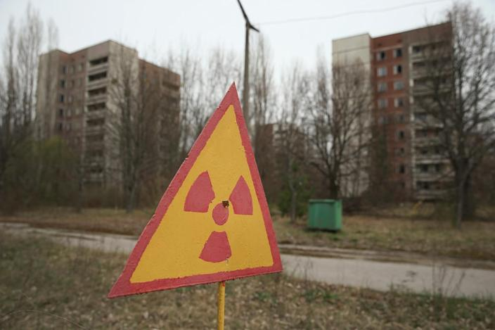 <p>A sign warns of radiation contamination near former apartment buildings (Getty Images) </p>