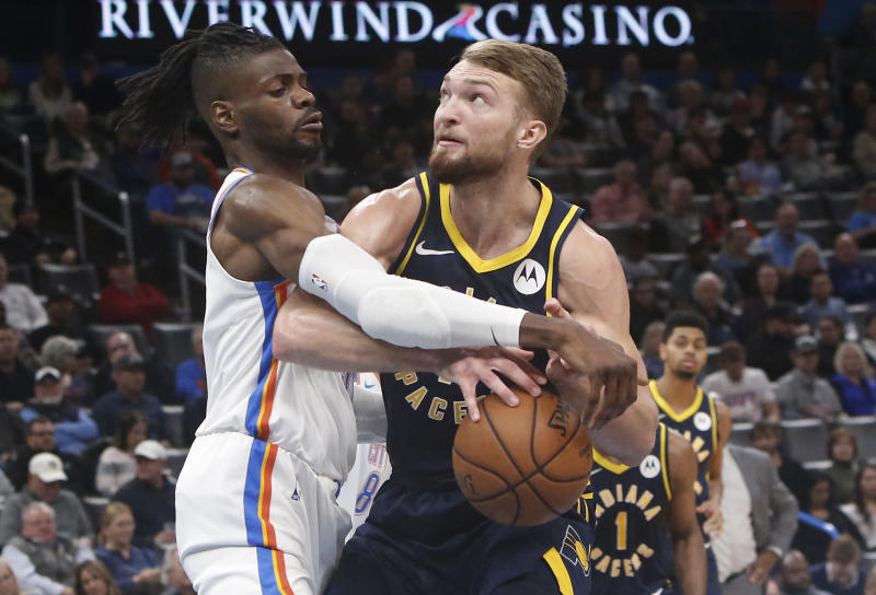 Oklahoma City Thunder center Nerlens Noel, left, knocks the ball away from Indiana Pacers forward Domantas Sabonis during the first half of an NBA basketball game Wednesday, Dec. 4, 2019, in Oklahoma City. (AP Photo/Sue Ogrocki)