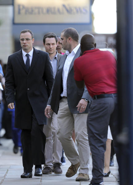 Oscar Pistorius, left, accompanied by his relatives, walks towards the high court in Pretoria, South Africa, Tuesday, April 8, 2014. Pistorius, who is charged with murder for the shooting death of his girlfriend, Reeva Steenkamp, on Valentines Day in 2013, was testifying for a second day at his murder trial Tuesday, answering questions from his defense lawyer. (AP Photo/Themba Hadebe)