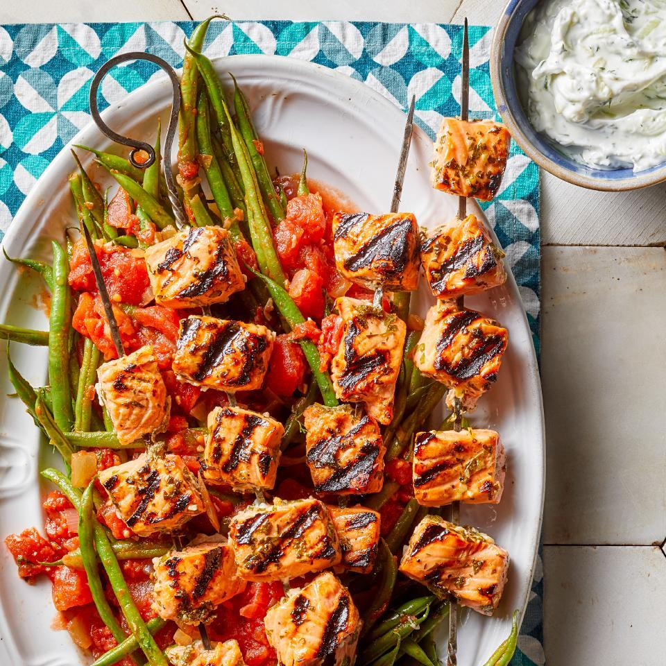 "<p>This easy grilled salmon recipe is sure to help you win your next backyard BBQ. Lemon, garlic and herbs make a simple, flavorful marinade for the healthy fish souvlaki (souvlakia is the Greek word for kebabs), and the yogurt-based tzatziki sauce is one of the traditional pleasures of Mediterranean cuisine. A side of Greek-style green beans completes this healthy dinner recipe that's as suited to entertaining as it is to family meals. <a href=""http://www.eatingwell.com/recipe/274831/greek-grilled-salmon-kebabs-with-tzatziki-green-beans/"" rel=""nofollow noopener"" target=""_blank"" data-ylk=""slk:View recipe"" class=""link rapid-noclick-resp""> View recipe </a></p>"
