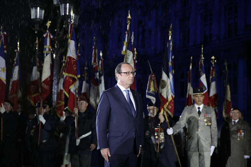 French President Francois Hollande reviews troops in front of Paris' town hall on August 25, 2014, during a ceremony to commemorate the 70th anniversary of the liberation of Paris from Nazi occupation during World War II