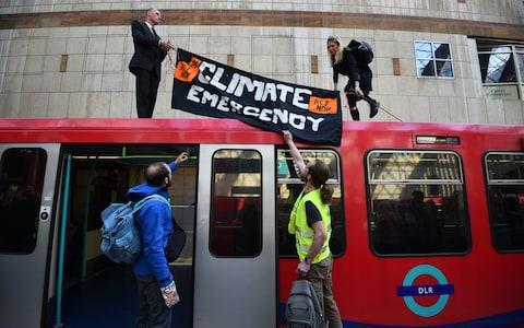 Climate activists on top of a Dockland Light Railway at Canary Wharf station in east London  - Credit:  Kirsty O'Connor/PA