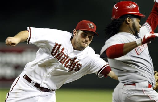 Arizona Diamondbacks first baseman Ryan Wheeler, left, tags out Cincinnati Reds' Johnny Cueto trying to bunt for a hit in the eighth inning during a baseball game, Tuesday, Aug. 28, 2012, in Phoenix. (AP Photo/Rick Scuteri)