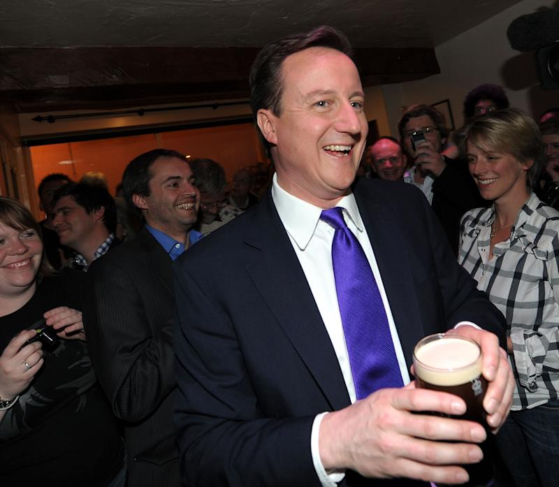 BRISTOL, ENGLAND - APRIL 22: Conservative Party Leader David Cameron holds a pint of Guinness as he stands with supporters at The Three Suga Loaves pub, following the second live televised debate between the three leaders of Britain's main political parties, on April 22, 2010 in Bristol, south-west England. The second of the three planned election debates, focused on global affairs, and aired live on Sky News from 20:00 BST. (Photo by Adrian Dennis - WPA Pool/Getty Images)