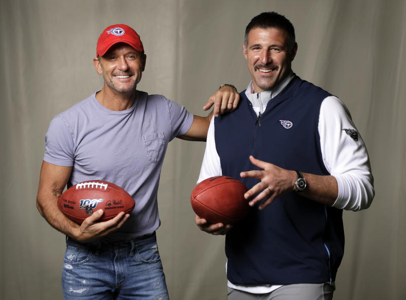 In this April 18, 2019, photo, country music star Tim McGraw, left, poses with Tennessee Titans head coach Mike Vrabel in Nashville, Tenn. After the opening round of the NFL Draft in Nashville on Friday, April 25, McGraw will cap off the evening performing on the draft stage across the Cumberland River from Nissan Stadium, home of the Tennessee Titans. (AP Photo/Mark Humphrey)