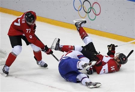 Canada's Chris Kunitz (14) falls over Norway's Alexander Bonsaksen as Canada's Jeff Carter attempts to dig out the puck during the third period of their men's preliminary round ice hockey game at the 2014 Sochi Winter Olympic Games, February 13, 2014. REUTERS/Grigory Dukor