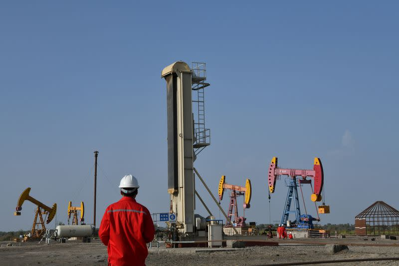 Workers are seen near pumpjacks at a CNPC oil field in Bayingol