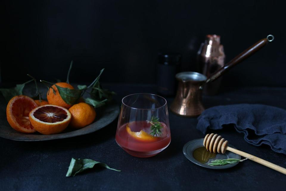 <p>The Brooklyn-based tastemaker, author, and stylist jazzes up the classic old fashioned with seasonal citrus and a delightful honey rosemary simple syrup that would make a thoughtful gift for your favorite cocktail connoisseurs. </p><p><strong>Athena's Blood Orange Old Fashioned</strong></p><p><strong>Ingredients:<em><br></em></strong></p><p><strong><em>For the Honey Rosemary Simple Syrup:</em><br></strong></p><p>1 cup water</p><p>1/2 cup honey</p><p>1 sprig rosemary</p><p><strong><em>For the cocktail:</em></strong></p><p>1/2 ounce bourbon</p><p>1 ounces blood orange juice</p><p>2-3 dashes aromatic bitters</p><p>1 tablespoon honey rosemary simple syrup</p><p>1 oversized ice cube</p><p><strong>Directions:</strong></p><p><em>To make the simple syrup: </em>Bring water, rosemary, and honey to a low boil and simmer for five minutes.</p><p><em>To make the cocktail: </em>Place bourbon, blood orange juice, aromatic bitters, and honey rosemary simple syrup in a cocktail shaker to gently combine. Pour over ice cube in a classic whiskey glass. </p>