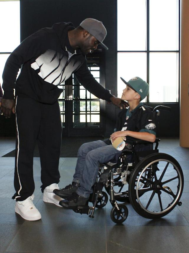 In this Oct. 18, 2013 photo, Philadelphia eagles quarterback Michael Vick greets seven-year-old Justin Perales before taking him on a tour of the Eagles training facility in Philadelphia. Four years after his release from prison, Vick is one of the NFL's most active players involving charities. Though he's no longer the starting quarterback for the Eagles, he's unquestionably the team leader. (AP Photo/ Joseph Kaczmarek)