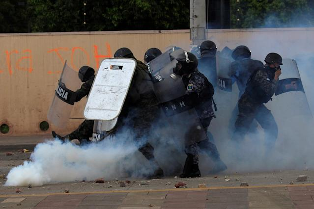 <p>Military policemen react to a gas canister thrown back by a supporter of Salvador Nasralla, presidential candidate for the Opposition Alliance Against the Dictatorship, during a protest caused by the delayed vote count for the presidential election in Tegucigalpa, Honduras, Nov. 30, 2017. (Photo: Jorge Cabrera/Reuters) </p>