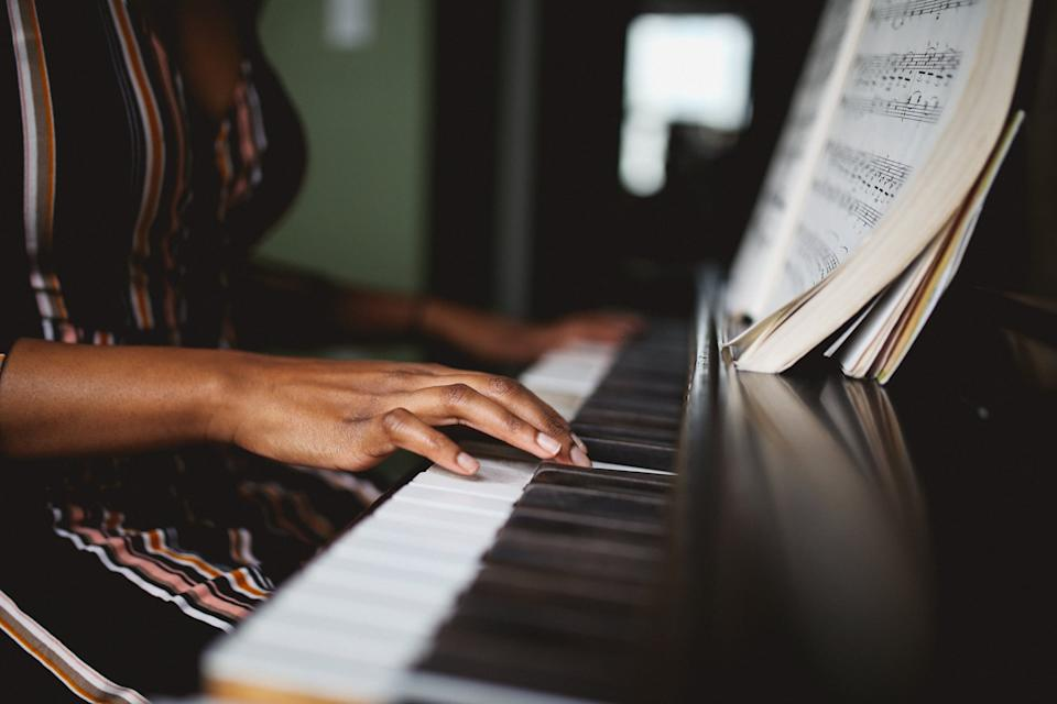 Retro toned, low key portrait of a young mixed race Latina woman practicing piano in her room in Downtown Los Angeles.