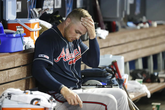 Atlanta Braves relief pitcher Sean Newcomb sits in the dugout during the eighth inning of a baseball game against the Miami Marlins, Sunday, Aug. 11, 2019, in Miami. Newcomb kicked a garbage can after giving up the winning run in the 10th inning of Saturday night's 7-6 loss to the Marlins. The metal garbage can hit the fire extinguisher hanging nearby on the tunnel wall between the dugout and clubhouse, and chemical dust began to spew. (AP Photo/Wilfredo Lee)