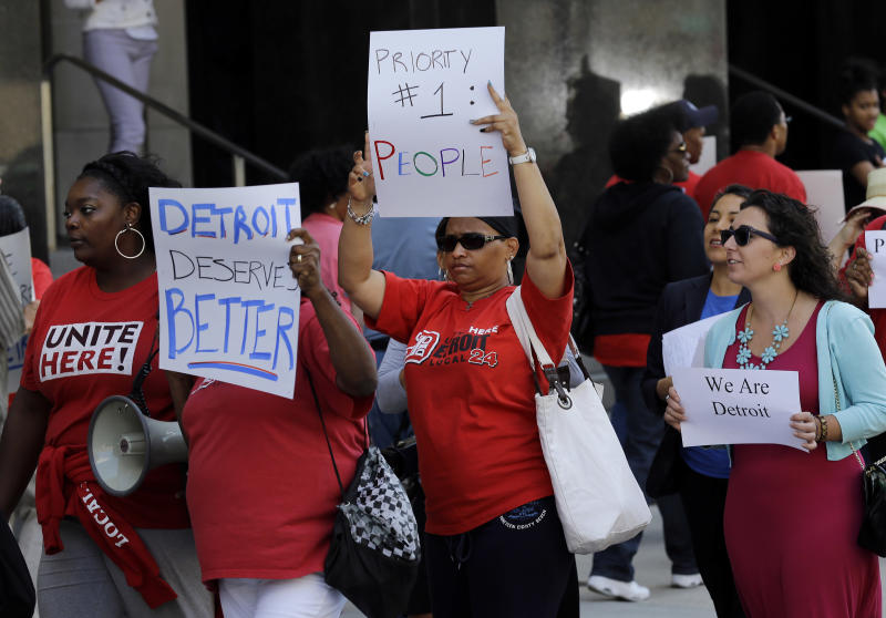 Protesters march outside the Theodore Levin United States Courthouse, in Detroit, Wednesday, July 24, 2013. A federal judge agreed with Detroit on Wednesday and stopped any lawsuits challenging the city's bankruptcy, declaring his courtroom the exclusive venue for legal action in the largest filing by a local government in U.S. history. (AP Photo/Paul Sancya)