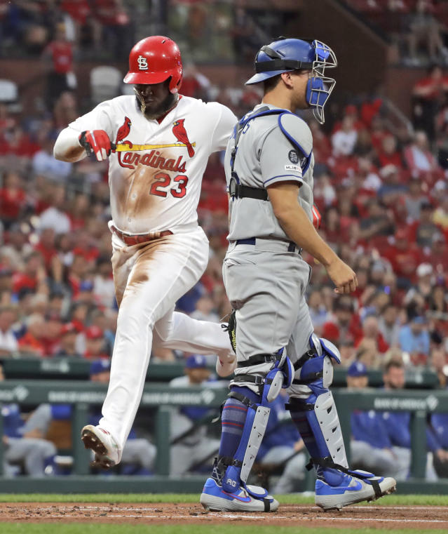 St. Louis Cardinals' Marcell Ozuna (23) scores past Los Angeles Dodgers catcher Austin Barnes during the second inning of a baseball game Wednesday, April 10, 2019, in St. Louis. (AP Photo/Jeff Roberson)