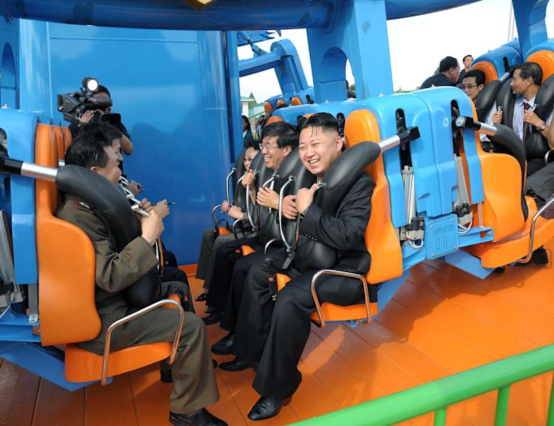 In this undated photo released by the Korean Central News Agency (KCNA) and distributed in Tokyo by the Korea News Service Thursday, July 26, 2012, North Korean leader Kim Jong Un, center, reacts on a ride as he attends the completion ceremony of the Rungna People's Pleasure Ground in Pyongyang. (AP Photo/Korean Central News Agency via Korea News Service) JAPAN OUT UNTIL 14 DAYS AFTER THE DAY OF TRANSMISSION