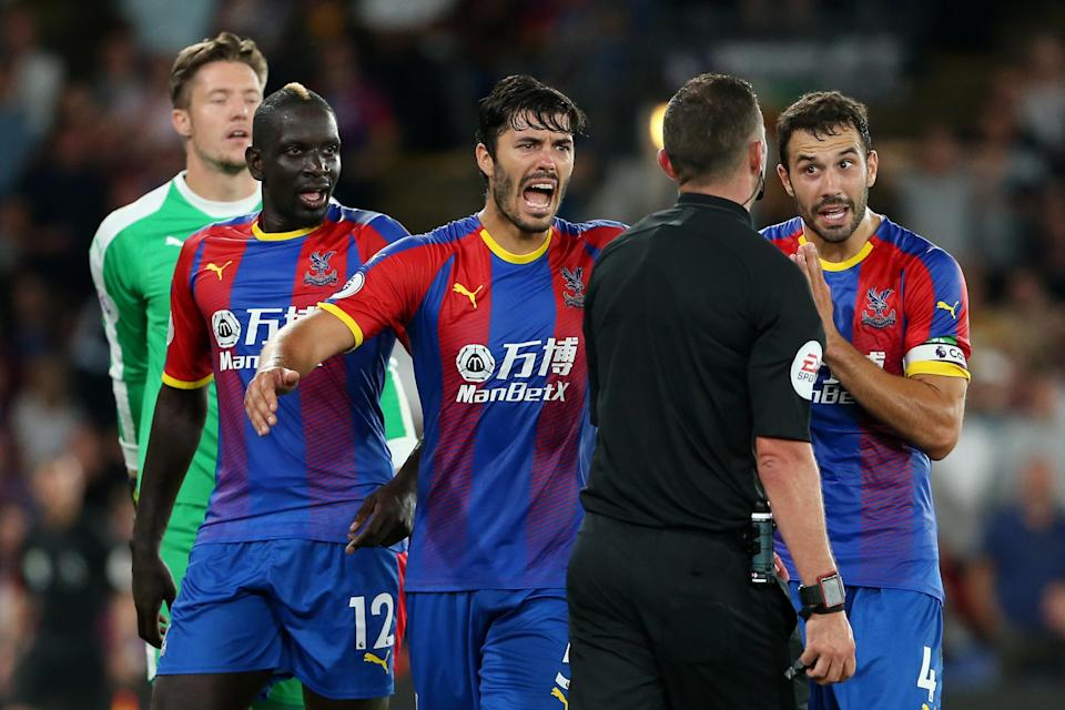 Palace players James Tomkins (C), Mamadou Sakho (L) and Luka Milivojevic (R) argue with referee Michael Oliver.