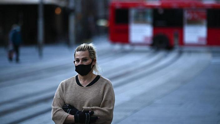 A woman wearing a mask stands in the middle of a road in central Sydney