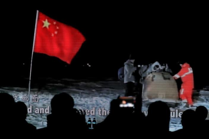 Screen shows a footage of reentry module carrying lunar samples landing on the earth during Chang'e-5 Mission, at an event in Beijing