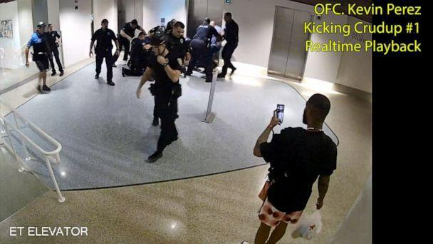PHOTO: Officer Kevin Perez is seen as he motions to kick Dalonta Crudup while Khalid Vaughn stands on the far right recording video with his phone, in an image taken from hotel surveillance video released by the Miami-Dade State Attorney's Office. (iami-Dade State Attorney's Office)