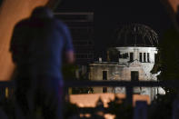 A visitor prays in front of the Atomic Bomb Dome in Hiroshima, western Japan early Friday, Aug. 6, 2021. Hiroshima on Friday marked the 76th anniversary of the world's first atomic bombing of the city. (Kyodo News via AP)