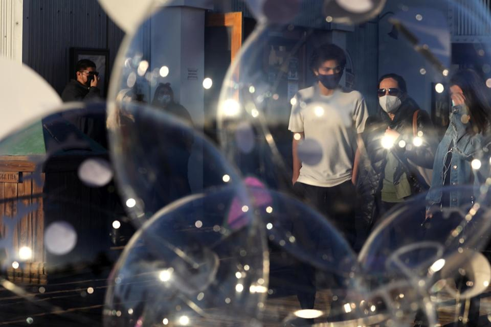 A family wearing masks walks behind a cluster of transparent balloons