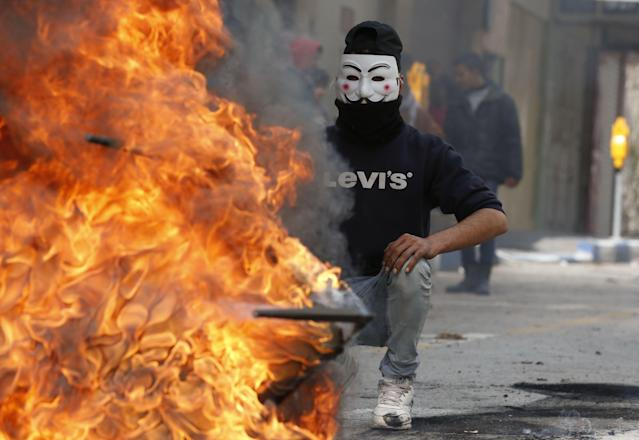 <p>A Palestinian protester wears a Guy Fawkes mask used by the anonymous movement during clashes with Israeli troops on Dec. 7, 2017 in Hebron in the Israeli-occupied West Bank, following protests against a decision by U.S. President Donald Trump to recognise Jerusalem as the capital of Israel. (Photo: Hazem Bader/AFP/Getty Images) </p>