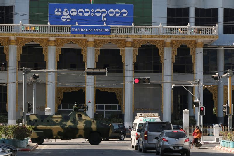 Myanmar army armoured vehicles drive past a street after they seized power in a coup in Mandalay