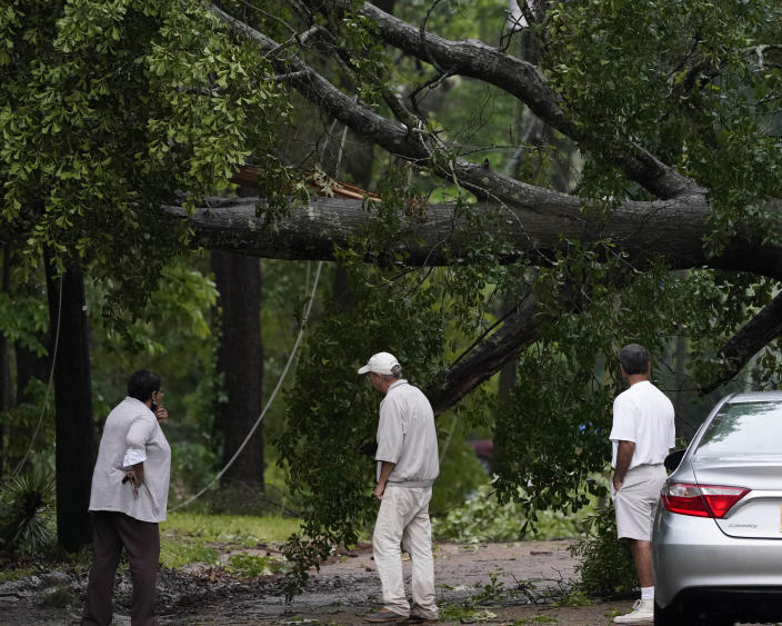 Neighbors inspect the wind toppled trees in this northeast Jackson, Miss., neighborhood, Tuesday, May 4, 2021. The severe weather was not unexpected, since the state was hit with a number of tornadoes on Sunday. (AP Photo/Rogelio V. Solis)