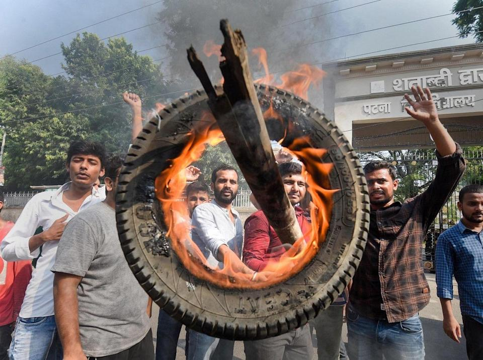 """<div class=""""paragraphs""""><p>Patna: People burn a tyre during their protest to support farmers Bharat Bandh against central governments three farm reform laws.</p></div>"""