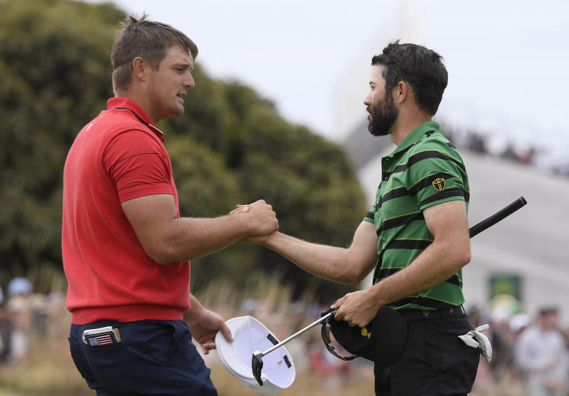 U.S. team player Bryson DeChambeau, left, and International team player Adam Hadwin of Canada shake hands after tying their singles match during the President's Cup golf tournament at Royal Melbourne Golf Club in Melbourne, Sunday, Dec. 15, 2019. (AP Photo/Andy Brownbill)
