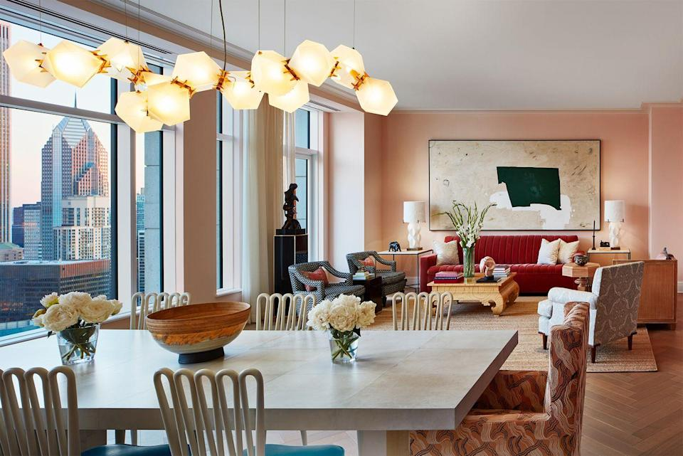 """<p>The open floor plan in this Chicago family apartment designed by <a href=""""https://www.brucefoxdesign.com/"""" rel=""""nofollow noopener"""" target=""""_blank"""" data-ylk=""""slk:Bruce Fox"""" class=""""link rapid-noclick-resp"""">Bruce Fox</a> called for cohesion between the dining and living room areas. That soft peachy paint and deep pink sofa are reflected in the printed armchair at the head of the dining table and also mimic the rosy glow of the pendant light. The color scheme was inspired by a photograph taken of the family in London during spring when the city was veiled in cherry blossoms. </p>"""
