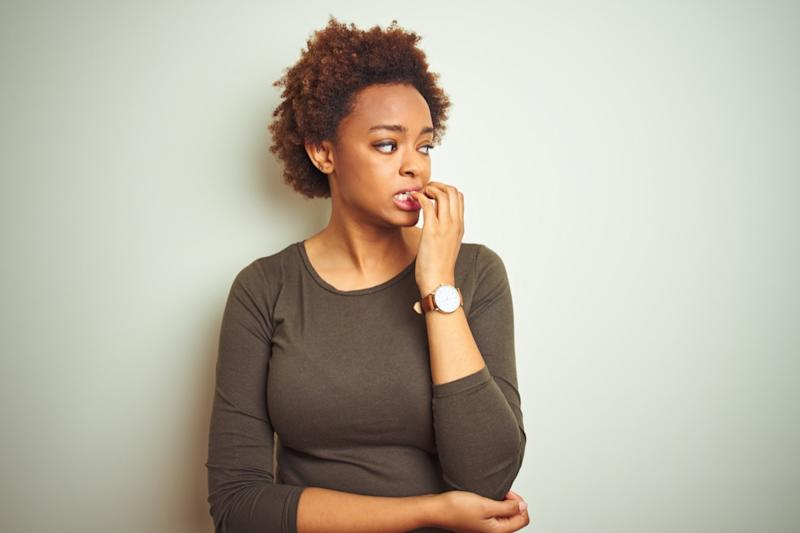 woman with afro hair over isolated background looking stressed and nervous with hands on mouth biting nails