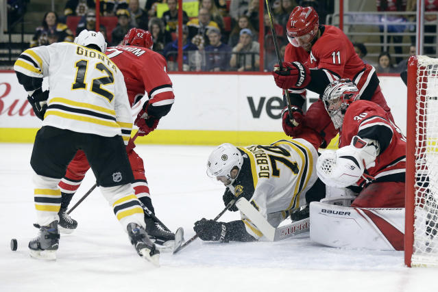 Boston Bruins' Jake DeBrusk (74) and Brian Gionta (12) try to take a shot against Carolina Hurricanes goalie Cam Ward (30) and Jordan Staal (11) during the first period of an NHL hockey game in Raleigh, N.C., Tuesday, March 13, 2018. (AP Photo/Gerry Broome)