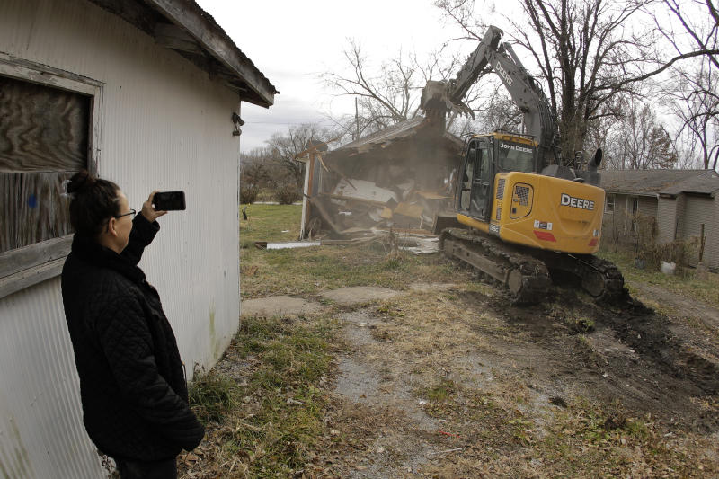 In this photo taken Monday, Nov. 18, 2019, Tammy Kilgore watches while her former home is demolished as part of a voluntary buyout in flood-prone Mosby, Mo. Kilgore accepted a $45,000 payment to leave her home of 38 years and has moved to a nearby community. (AP Photo/Charlie Riedel)