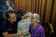 Thai surgeon Sakirin Al-Ishak prepares Somprasong Aimsantia for plastic surgery on her nose at the Vayo Clinic in Bangkok