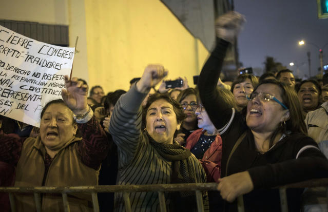 Demonstrators who had gathered to protest against lawmakers pushing forward a vote to select an almost-full slate of new magistrates to the Constitutional Tribunal, celebrate outside Congress after President Martin Vizcarra dissolved the legislature in Lima, Peru, Monday, Sept. 30, 2019. Lawmakers were pushing forward the vote despite Vizcarra's warning that the move threatens his fight against corruption and that he would dissolve the opposition-controlled legislature. (AP Photo/Rodrigo Abd)