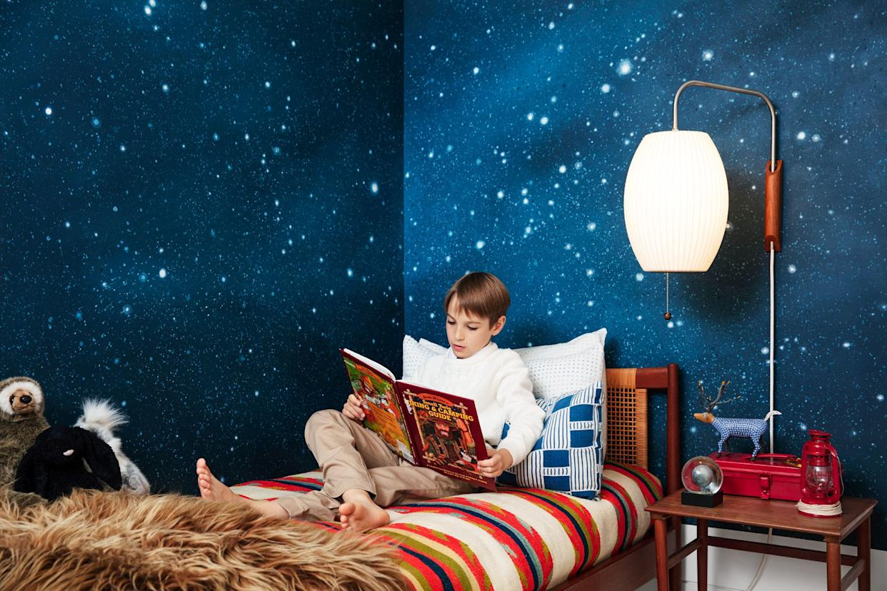 """<div class=""""caption""""> Asher reads beneath a George Nelson bubble sconce. Night sky wall mural by <a href=""""http://azmuralsanddecorativepainting.com"""" rel=""""nofollow noopener"""" target=""""_blank"""" data-ylk=""""slk:Ashley Zangle"""" class=""""link rapid-noclick-resp"""">Ashley Zangle</a>. </div>"""