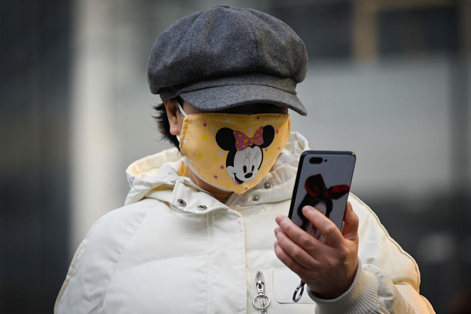 """A woman wearing a Minnie Mouse face mask looks at her mobile phone in Beijing on February 11, 2020. - The death toll from a new coronavirus outbreak surged past 1,000 on February 11 as the World Health Organization warned infected people who have not travelled to China could be the spark for a """"bigger fire"""". (Photo by STR / AFP) (Photo by STR/AFP via Getty Images)"""