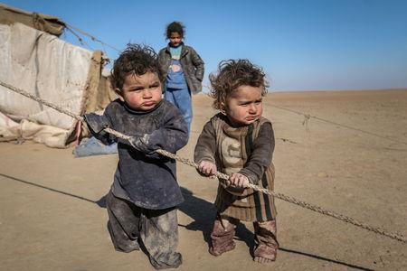FILE PHOTO: Internally displaced Syrian children who fled Raqqa city stand near their tent in Ras al-Ain province, Syria, January 22, 2017. REUTERS/Rodi Said//File Photo