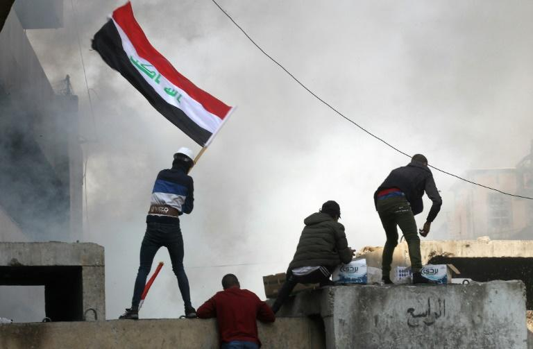 Protesters wave the Iraqi flag amid clashes in Baghdad's Al-Rasheed street on November 26, 2019