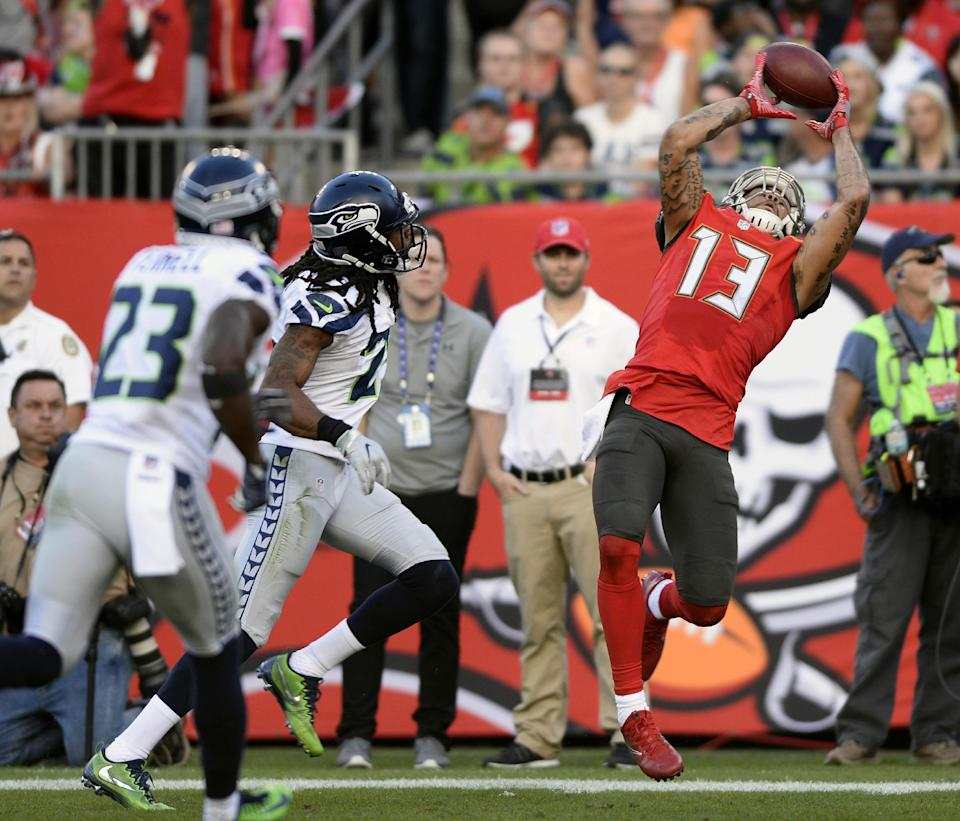 <p>Tampa Bay Buccaneers wide receiver Mike Evans (13) catches a 23-yard touchdown reception in front of Seattle Seahawks cornerback Richard Sherman (25) and free safety Steven Terrell (23) during the first quarter of an NFL football game Sunday, Nov. 27, 2016, in Tampa, Fla. (AP Photo/Jason Behnken) </p>