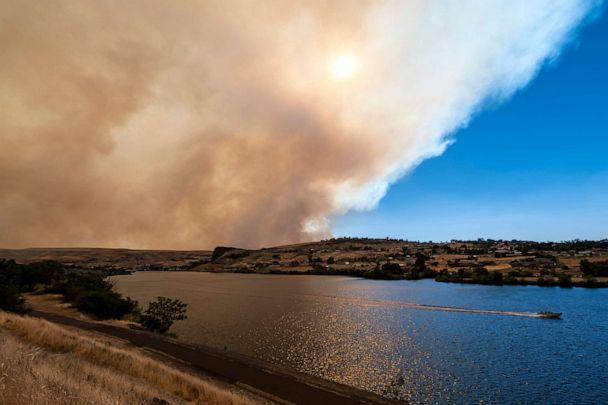 PHOTO: A boat heads down the Snake River as smoke from the Asotin Complex Fire west of Clarkston, Wash., wafts eastward into Lewiston, Idaho, on July 7, 2021. (Pete Caster/The Lewiston Tribune via AP)