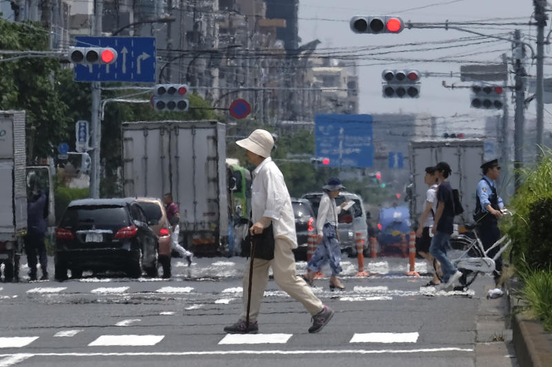 Heat haze distorts the background as pedestrians walk past during a heatwave in Tokyo on July 31, 2019. (Photo by Kazuhiro NOGI / AFP) (Photo credit should read KAZUHIRO NOGI/AFP/Getty Images)