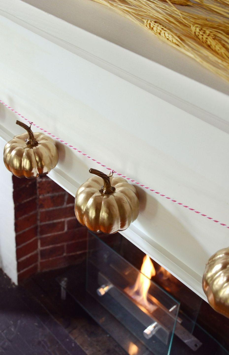 """<p>Sure, pumpkins are naturally orange—but they might look a tad more chic in glimmering, glamorous gold. </p><p><strong>Get the tutorial at <a href=""""https://design-fixation.com/2018/08/sponsored-diy-fall-pumpkin-garland.html"""" rel=""""nofollow noopener"""" target=""""_blank"""" data-ylk=""""slk:Design Fixation"""" class=""""link rapid-noclick-resp"""">Design Fixation</a>.</strong></p><p><a class=""""link rapid-noclick-resp"""" href=""""https://go.redirectingat.com?id=74968X1596630&url=https%3A%2F%2Fwww.walmart.com%2Fip%2FGold-Rust-Oleum-American-Accents-2X-Ultra-Cover-Metallic-Spray-Paint-11-oz%2F258625409&sref=https%3A%2F%2Fwww.thepioneerwoman.com%2Fhome-lifestyle%2Fcrafts-diy%2Fg36891743%2Ffall-mantel-decorations%2F"""" rel=""""nofollow noopener"""" target=""""_blank"""" data-ylk=""""slk:SHOP GOLD SPRAY PAINT"""">SHOP GOLD SPRAY PAINT</a></p>"""
