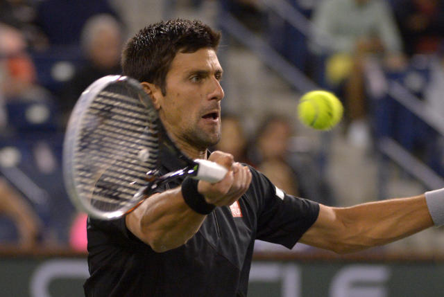 Novak Djokovic, of Serbia, returns a shot to Marin Cilic, of Croatia, during their match at the BNP Paribas Open tennis tournament, Wednesday, March 12, 2014, in Indian Wells, Calif. (AP Photo/Mark J. Terrill)