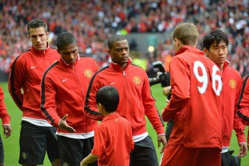 Manchester United defender Patrice Evra (3rd left) waits to shakes hands with Liverpool Steven Gerrard (2nd right) before the Premier League match in Liverpool. Ten-man Liverpool were left searching for their first Premier League win under new manager Brendan Rodgers as arch-rivals Manchester United came from behind to win 2-1 at an emotional Anfield