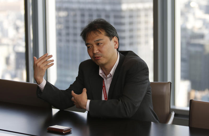 In this Wednesday, June 5, 2013 photo, Takashi Yamada, a government-bond trader at major brokerage Daiwa Securities Co., gestures during an interview in Tokyo. Until a couple of months ago, Yamada had one of the most genteel jobs in Japan. Now, his days are so harried he doesn't have time to eat lunch. Shock-and-Awe monetary policies, announced in April, have sent Japanese government bonds, this nation's equivalent of U.S. Treasurys, into a whirl of volatility.(AP Photo/Shuji Kajiyama)
