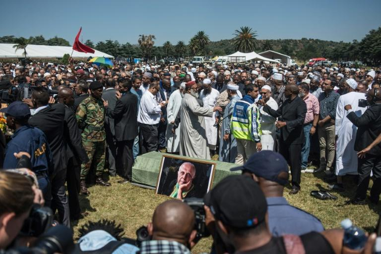 South African ruling party ANC leadership, opposition leaders and family members stand around the casket of late anti-apartheid activist Ahmed Kathrada during his funeral ceremony at the Westpark Cemetery in Johannesburg on March 29, 2017